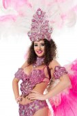 cheerful girl in carnival costume with pink feathers and gems, isolated on white