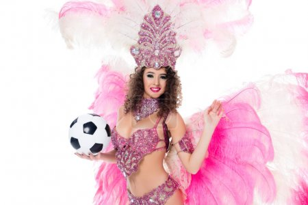 smiling woman in carnival costume with pink feathers holding soccer ball, isolated on white