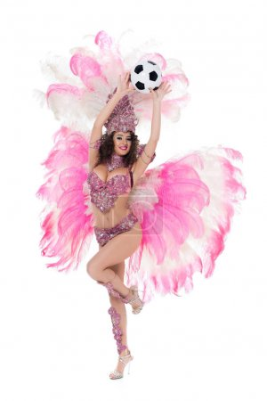woman in carnival costume with pink feathers holding soccer ball, isolated on white