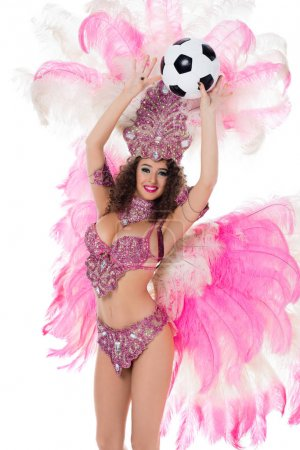 cheerful woman in carnival costume with pink feathers holding soccer ball, isolated on white