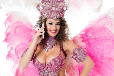 woman in carnival costume using smartphone and looking at camera, isolated on white