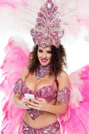woman in carnival costume using smartphone while looking at camera, isolated on white