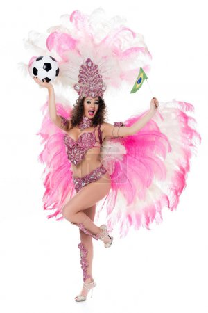 smiling woman in carnival costume holding football ball and brazilian flag while looking at camera, isolated on white