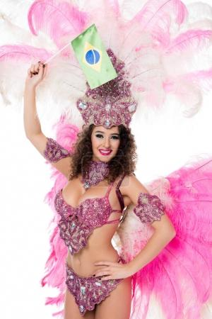 smiling woman in carnival costume holding brazilian fllag in raised hand, isolated on white
