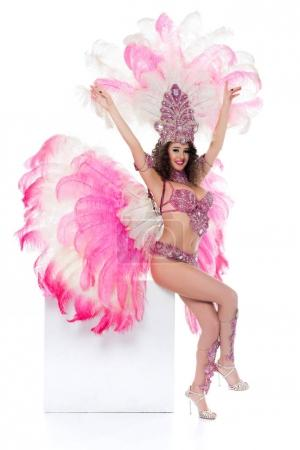 young woman in carnival costume sitting on blank square with arms raised, isolated on white