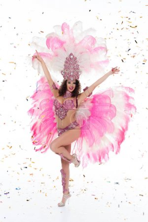 full length of woman in carnival costume surrounded by confetti, isolated on white