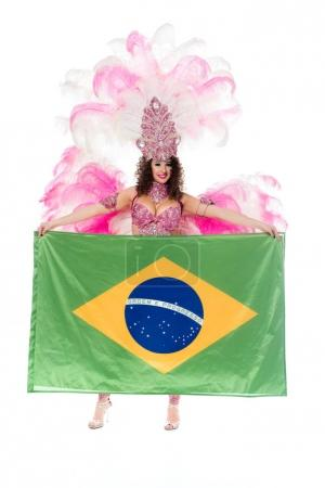 Happy young woman in carnival costume with pink feathers holds large flag of Brasil isolated on white