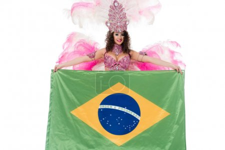 Bright woman in carnival costume with pink feathers holds large flag of Brasil isolated on white