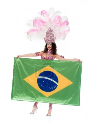 Bright woman in carnival costume with pink feathers holds flag of Brasil isolated on white