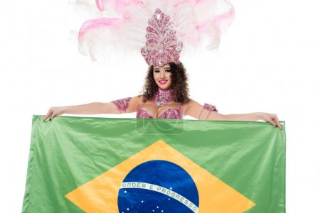 Cheerful woman in carnival costume with pink feathers holds flag of Brasil isolated on white