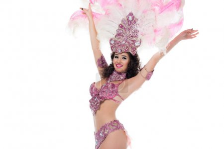 Cheerful woman in carnival costume with pink feathers with hands raised elated isolated on white