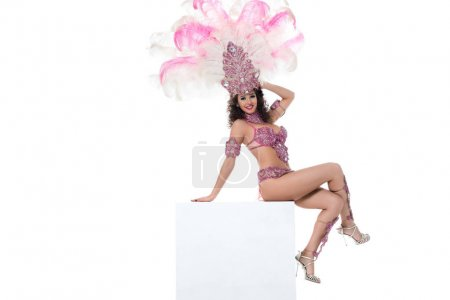 Young happy woman in carnival costume with pink feathers sitting with arm behind head isolated on white