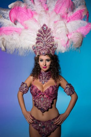 Bright woman in carnival costume with pink feathers isolated on blue background