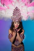 Bright woman in carnival costume with pink feathers sending air kiss isolated on blue background