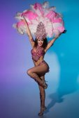 Bright woman in carnival costume with pink feathers performs on blue background