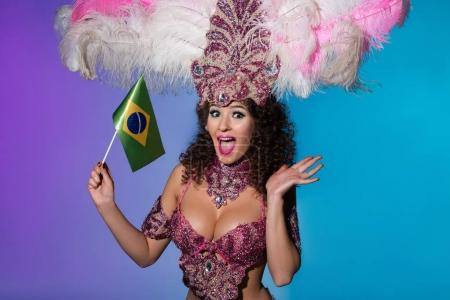 Cheerful woman in carnival costume with pink feathers holding flag of Brasil isolated on blue background