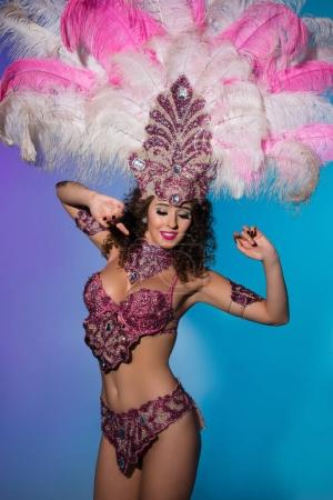 Happy young woman in carnival costume with pink feathers on blue background