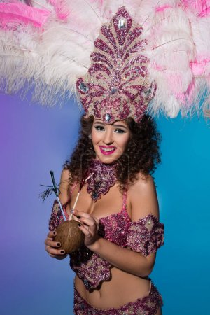 Bright woman in carnival costume with pink feathers drinking from whole coconut isolated on blue background