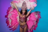 Cheerful woman in carnival costume with pink feathers raising hands isolated on blue background