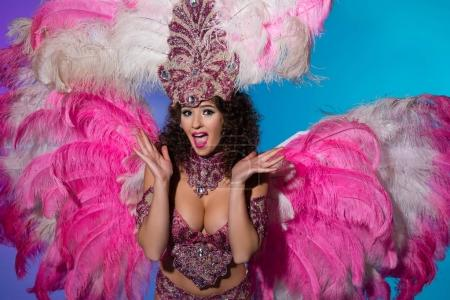 Surprised young woman in carnival costume with pink feathers isolated on blue background