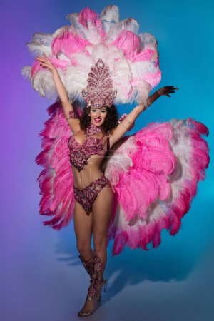 Bright woman in carnival costume with pink feathers on blue background