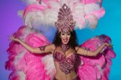 Happy young woman in carnival costume with pink feathers isolated on blue background