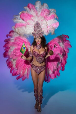 Cheerful woman in carnival costume with pink feathers holding coconut and Brasil flag on blue background