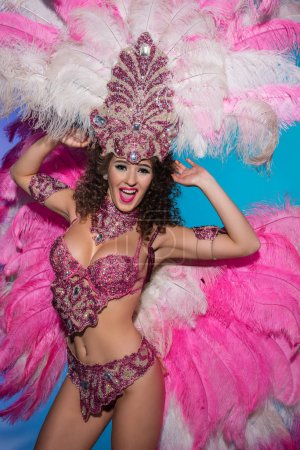 Happy young woman in carnival costume with pink feathers performing isolated on blue background