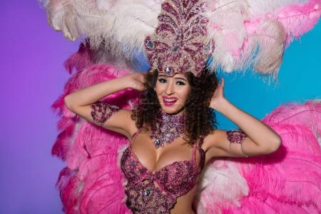 Bright woman in carnival costume with pink feathers dancing and smiling isolated on blue background