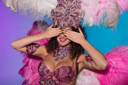 Cheerful woman in carnival costume with pink feathers covering her eyes isolated on blue background