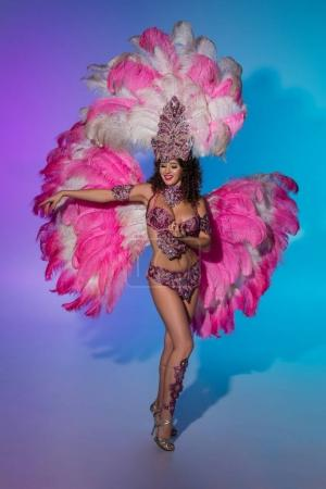 Bright woman in carnival costume with pink feathers performing on blue background