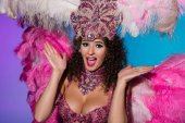 Cheerful woman in carnival costume with pink feathers laughing isolated on blue background