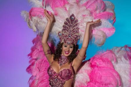 Happy young woman in carnival costume with pink feathers smiling elated isolated on blue background
