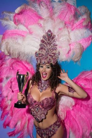 Bright woman in carnival costume with pink feathers  holding winner cup isolated on blue background
