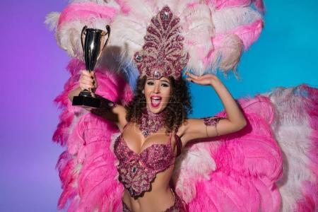 Happy young woman in carnival costume with pink feathers holding winner cup isolated on blue background