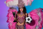 Cheerful woman in carnival costume with pink feathers holding soccer ball and winner cup on blue background