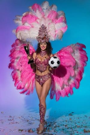 Happy young woman in carnival costume with pink feathers holding soccer ball and winner cup on blue background