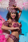 Bright woman in carnival costume with pink feathers dancing and smiling on blue background