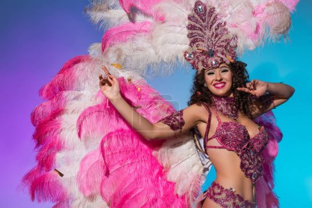 Cheerful woman in carnival costume with pink feathers dancing and smiling isolated on blue background