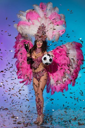 Bright woman in carnival costume with pink feathers holding soccer ball and winner cup on blue background