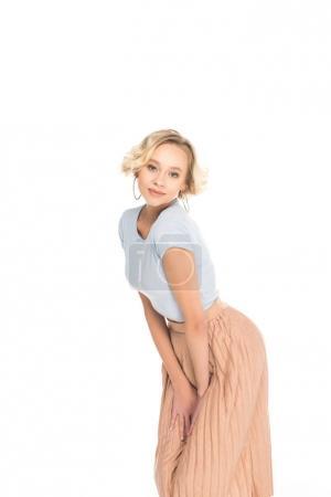 bonita chica rubia en falda rosa posando y mirando a la cámara aislada en blanco