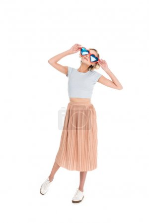 full length view of beautiful young woman in heart shaped sunglasses posing isolated on white