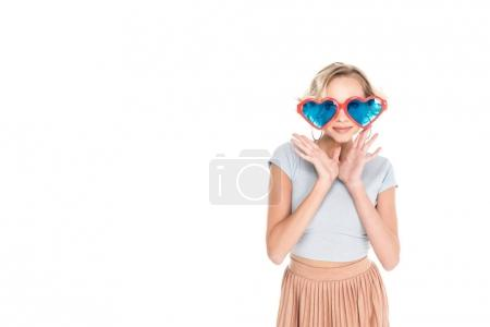 beautiful young woman in big heart shaped sunglasses posing isolated on white