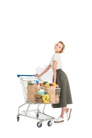 cheerful young woman standing with shopping trolley and smiling at camera isolated on white