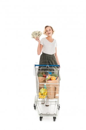 happy woman holding dollar banknotes and standing with shopping trolley full of grocery isolated on white