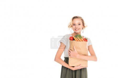 attractive happy young woman holding grocery bag and looking at camera isolated on white