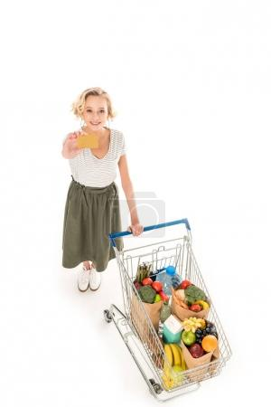 high angle view of young woman holding credit card and smiling at camera while standing with shopping trolley full of grocery isolated on white