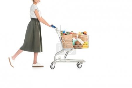 partial side view of woman pushing shopping trolley with grocery bags isolated on white