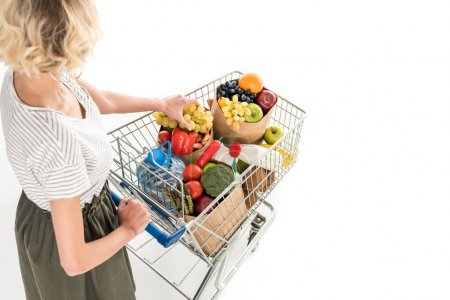 cropped shot of young woman pushing shopping trolley with grocery bags and plastic bottle of water isolated on white