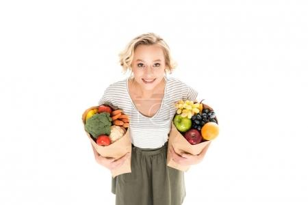 high angle view of beautiful young woman smiling at camera while standing with paper bags full of fresh fruits and vegetables isolated on white